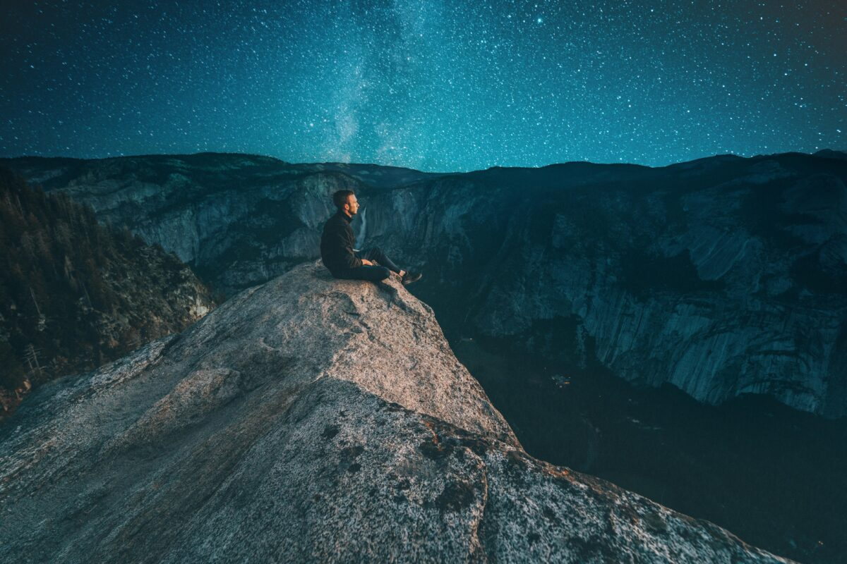 Man on the edge of a mountain with stars